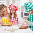 Woman and her daughters in the kitchen - Stock Photo