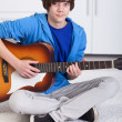 Young teenager boy playing the guitar — Stock Photo