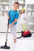 Kids cleaning the room - using a vacuum cleaner — Stock Photo