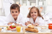 Kids having a healthy breakfast in bed — Stock Photo