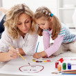 Little girl painting with her mother — Stock Photo