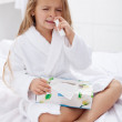 Little girl with a bad case of influenza using nasal spray — Stock Photo