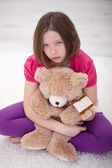 Sad young girl sitting with teddy bear — Stock Photo