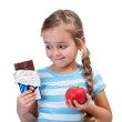 Diet choices - little girl with apple and chocolate — Stock Photo