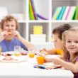Kids around the table eating — Stock Photo
