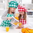 Stock Photo: Girls making freshly squezed orange juice