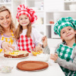 Kids and their mother making a cake - Stock Photo