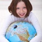 Young girl hugging earth globe — Stock Photo