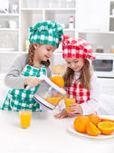 Girls making freshly squezed orange juice — Stock Photo