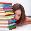 Young girl hiding behind books — Stock Photo