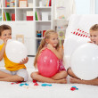 Kids blowing up balloons - Stock Photo