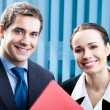 Two happy businesspeople with folder at office — Stock Photo