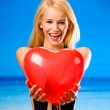 Woman with valentine's balloon on beach — Stock Photo #10472870