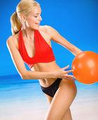 年轻女子在沙滩上玩球 — 图库照片