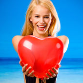Woman with valentine's balloon on beach — Stock Photo