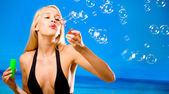 Young woman blowing bubbles on beach — Stok fotoğraf