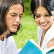 Young couple or students, reading a book — Stock Photo