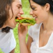 Young couple eating together outdoors — Stock Photo