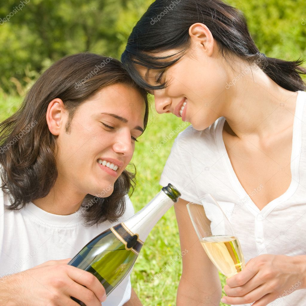 Young happy smiling cheerful attractive couple celebrating with glasses of champagne, outdoor — Stock Photo #10674143