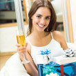 Woman with champagne and gifts at home — Stock Photo #8416941