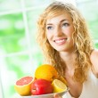 Woman with plate of fruits, indoors — Stock Photo #8417483