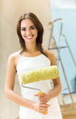 Happy woman with paint roller in new house — Stock Photo