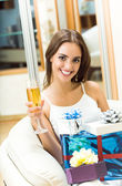 Woman with champagne and gifts at home — Stock Photo