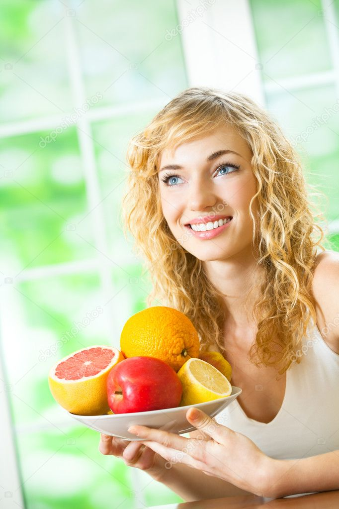 Young happy smiling beautiful woman with plate of fruits, indoors — Stock Photo #8417483