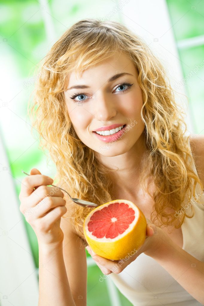 Portrait of young happy smiling woman eating grapefruit at home — Stock Photo #8417495