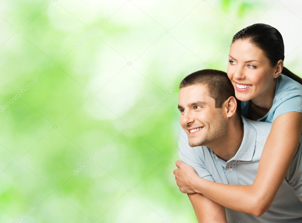 Portrait of young happy smiling attractive couple outdoors, with copyspace — Stock Photo #8417893