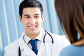 Young female patient and happy doctor at office — Stock Photo