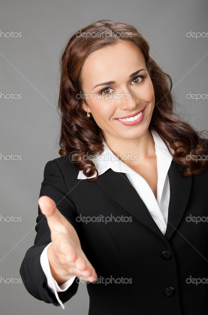 Portrait of young cheerful beautiful business woman giving hand for handshake, over grey background — Stock Photo #8989844