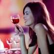 Stock Photo: Young womwith redwine at restaurant