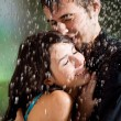 Young couple hugging under a rain - Stockfoto
