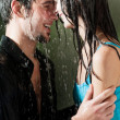 Stock Photo: Young couple hugging under a rain