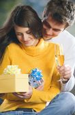 Couple with champagne and gifts — Stock Photo