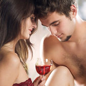 Young enamoured couple drinking red wine on the bed in bedroom — Stock Photo