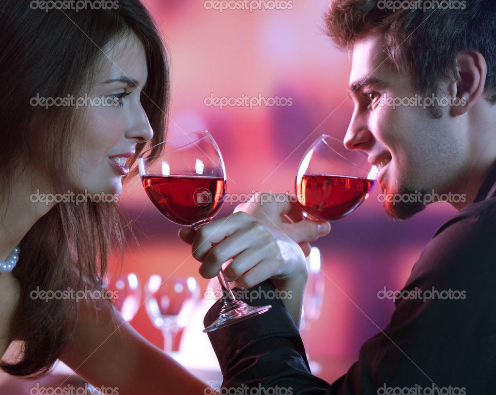 Young happy amorous couple with glasses of redwine on romantic date at restaurant — Stock Photo #9615489
