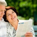 Happy senior couple reading outdoors — Stock Photo #9701231
