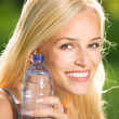 Young attractive woman with bottle of water outdoors — Stock Photo