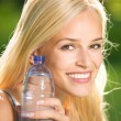 Stock Photo: Young attractive womwith bottle of water outdoors