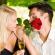 Couple with glasses of champagne and rose, outdoors — Stock Photo