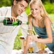 Young couple with champagne at picnic, outdoors — Stok fotoğraf #9706697