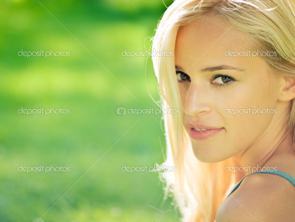 Portrait of smiling young beautiful blond woman outdoors, with copyspace  Stock Photo #9701316