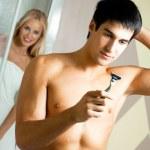 Shaving man and woman at bathroom — Stock Photo