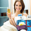 Woman with champagne and gifts at home — Stockfoto