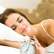 Woman with alarmclock lying on bed, at home — Stock Photo
