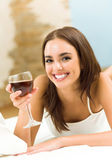 Woman with glass of red wine, on bed — Stock Photo