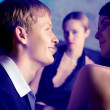 Young couple and woman looking at them at club - Foto Stock