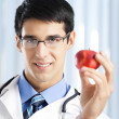 Smiling doctor with apple, at office - Stockfoto